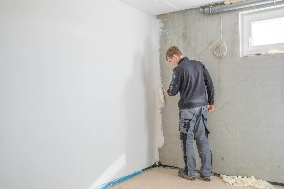 Junger Handwerker trägt mit Handrolle weiße Wandfarbe auf eine Kellerwand auf