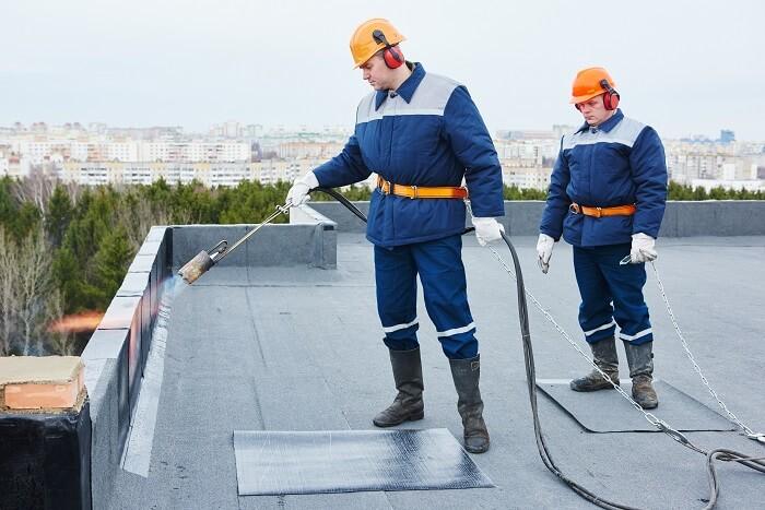 Zwei Bauarbeiter in persönlicher Schutzausrüstung für Bitumenverlegearbeiten versiegeln die Schutzbeschichtungen an der Dachkante